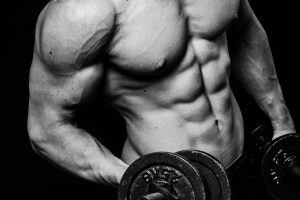 Close up of muscular bodybuilder guy doing exercises with weights dumbbell over isolated black