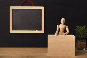 Wooden marionette sitting in classroom