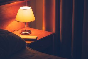 Book and vintage lamp on night table in hotel room