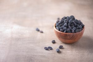 Black raisins in wooden bowl on wood textured background. Copy space. Superfood, vegan, vegetarian