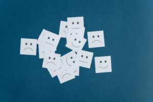 Many white post it papers with smiling sad and neutral faces on them
