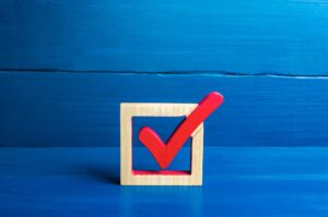 Red voting check mark on a blue background. Voting concept for democratic elections