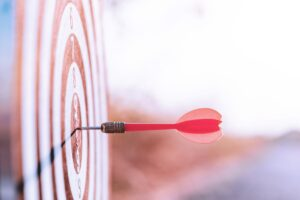 Close up red dart arrow hitting target center dartboard on sunset background. Business targeting and