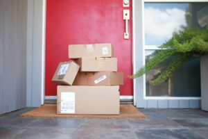 Delivered packages stacked on the porch against a red door