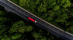 Red truck on the long road through the green forest. Photo by drone from above