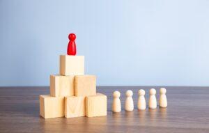 Wooden people figures on top of wooden blocks. Career growth, development and leadership